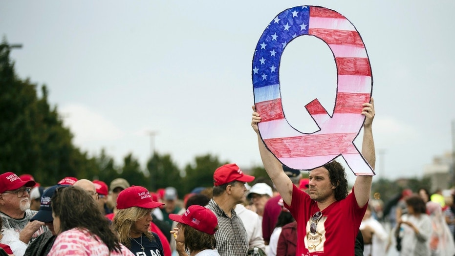 A man holds a 'Q' sign while waiting to enter a Pennsylvania rally with President Trump.