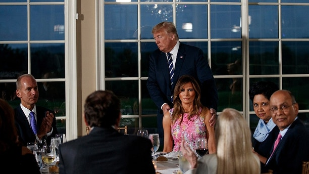 President Donald Trump walks to his seat between first lady Melania Trump, right, and Boeing Co. Chairman, President and CEO Dennis Muilenburg, left, after speaking at a dinner meeting with business leaders, Tuesday, Aug. 7, 2018, at Trump National Golf Club in Bedminster, N.J. Second from left is PepsiCo's departing CEO Indra Nooyi. (AP Photo/Carolyn Kaster)