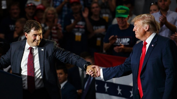 12th Congressional District Republican candidate Troy Balderson, left, reaches for President Donald Trump as he speaks at a rally at Olentangy Orange High School in Lewis Center, Ohio, Saturday, Aug. 4, 2018. (AP Photo/Carolyn Kaster)