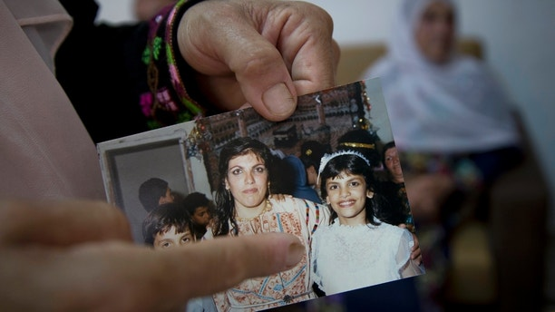 In this Wednesday, Aug. 8, 2018 photo, Fadwa Tlaib, an aunt of Rashida Tlaib points to a young Rashida in a 1987 picture with her mother Fatima and brother Nader, at the family house, in the West Bank village of Beit Ur al-Foqa. The Michigan primary victory of Tlaib, who is expected to become the first Muslim woman and Palestinian-American to serve in the U.S. Congress, is rippling across the Middle East. In the West Bank village where Tlaib's mother was born, residents are greeting the news with a mixture of pride and hope that she will take on a U.S. administration widely seen as hostile to the Palestinian cause. (AP Photo/Nasser Nasser)