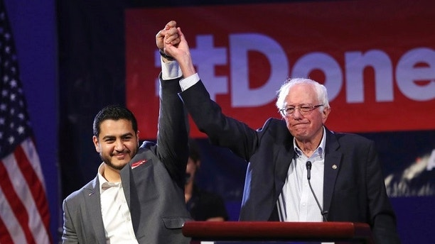 Michigan Democratic gubernatorial candidate Dr. Abdul El-Sayed, left, and Sen. Bernie Sanders raise their arms after addressing supporters during a rally for El-Sayed, Sunday, Aug. 5, 2018, in Detroit. (AP Photo/Carlos Osorio)