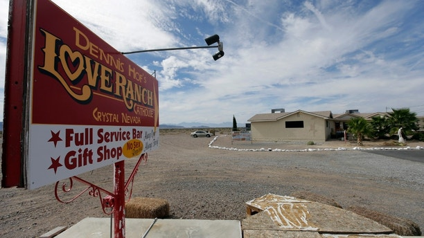 FILE - In this Oct. 14, 2015, file photo, a sign advertises Dennis Hof's Love Ranch brothel in Crystal, Nev. County officials in Nevada have yanked a brothel license from the state's most famous pimp who has fashioned himself as a Donald Trump-style candidate for Nevada's legislature. Officials in Southern Nevada's Nye County on Tuesday said Dennis Hof had failed to apply for a renewal and pay fees for his Love Ranch brothel in Crystal, about an hour's drive northwest of Las Vegas. (AP Photo/Chris Carlson, File)