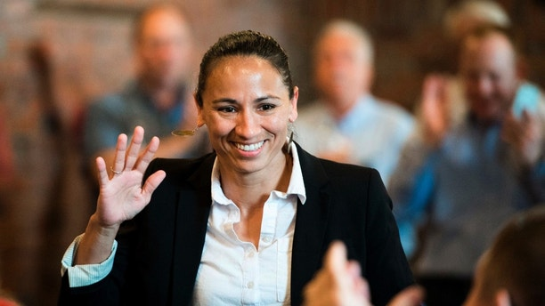 Democrat Sharice Davids waves at her supporters at a Democratic event in Kansas City, Kan., Wednesday, Aug. 8, 2018. She added her name Wednesday to her party's increasingly diverse slate of candidates advancing to the November ballot. Davids, who would be the first gay, Native American elected to Congress, narrowly won a six-way primary in her eastern Kansas district, shattering the mold for a congressional primary winner in conservative Kansas and embodying the range of ethnicities and sexual orientations of Democratic candidates running throughout the country this fall. (Shelly Yang/The Kansas City Star via AP)