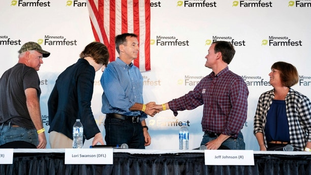 Minnesota gubernatorial candidates Tim Pawlenty, center left, and Jeff Johnson shake hands as fellow candidates look on at the end of a forum ahead of next week's primary at the annual FarmFest in Redwood Falls, Minn. Wednesday, Aug. 8, 2018. (Glen Stubbe/Star Tribune via AP)