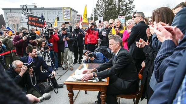 FILE - In this April 11, 2018 file photo, Vermont Gov. Phil Scott finishes signing a gun restrictions bill on the steps of the Statehouse in Montpelier, Vt. Scott faces a challenge by Springfield businessman Keith Stern in the Aug. 14, 2018, Republican primary.