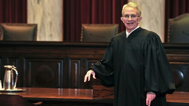 FILE - In this Jan. 5, 2012 file photo, West Virginia Supreme Court of Appeals Chief Justice Menis Ketchum poses in his robe in the court chambers in Charleston, W. Va. West Virginia Supreme Court Justice Menis Ketchum plans to resign and retire two years before his term ends, Gov. Jim Justice said Wednesday, July 11, 2018. (Bob Wojcieszak/Charleston Gazette-Mail via AP, File)