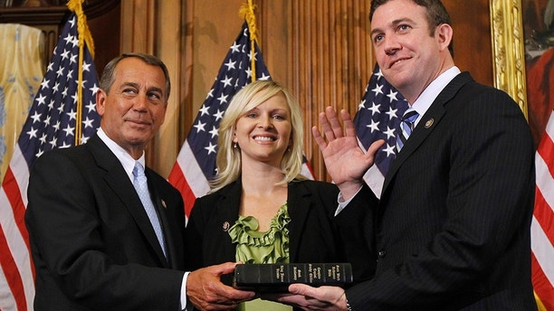 House Speaker John Boehner of Ohio, left, administers the House oath to Rep. Duncan Hunter, R-Calif., during a mock swearing-in ceremony on Capitol Hill in Washington, Wednesday, Jan. 5, 2011. (AP Photo/Alex Brandon)