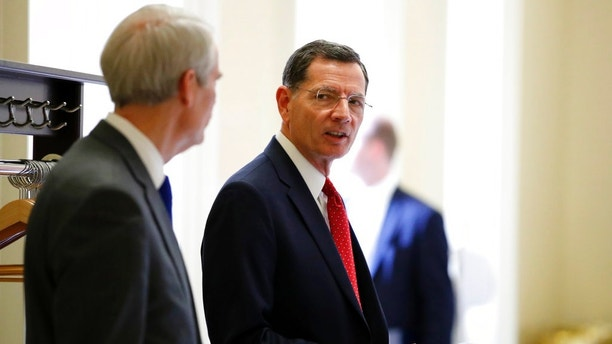 FILE - In this March 20, 2018, file photo, Sen. John Barrasso, R-Wyo., right speaks with Sen. Rob Portman, R-Ohio, after a Republican policy luncheon on Capitol Hill in Washington. On Tuesday, Aug. 21, 2018, Barrasso fended off a well-funded challenger in Wyoming's Republican primary and will face Wilson businessman Gary Trauner in the general election. Trauner ran unopposed for the Democratic nomination. (AP Photo/Jacquelyn Martin, File)