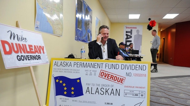 Republican gubernatorial candidate Mike Dunleay reaches out by phone Tuesday, Aug. 21, 2018, in Anchorage, Alaska. Dunleavy, a former state senator, is one of seven Republicans vying in the Alaska Primary. The winner advances to the general election and is expected to face incumbent Gov. Bill Walker, an independent, and former U.S. Sen. Mark Begich, a Democrat. (AP Photo/Michael Dinneen)