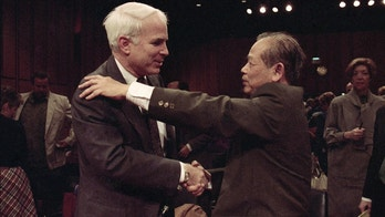 """FILE - In this Nov. 7, 1991, file photo, Sen. John McCain, R-Ariz., left, is hugged by former North Vietnam Col. Bui Tin on Capitol Hill in Washington after a hearing of the Senate Select Committee on POW and MIA affairs. Tin oversaw a military prison operation dubbed the """"Hanoi Hilton,"""" where McCain was held prisoner during the Vietnam War. McCain, the war hero who became the GOP's standard-bearer in the 2008 election, died Saturday, Aug. 25, 2018. He was 81. (AP Photo/Dennis Cook, File)"""