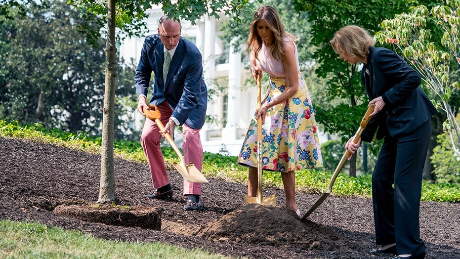 Richard Emory Gatchell, Jr., first lady Melania Trump, and Mary Jean Eisenhower participate in a presidential tree planting ceremony on the South Lawn of the White House