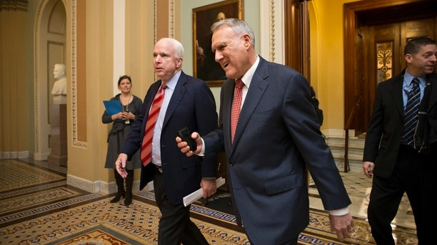 """FILE - In this Dec. 30, 2012, file photo, Sen. John McCain, R-Ariz., left, and Senate Minority Whip Jon Kyl, R-Ariz., leave the chamber as the Senate rushes to negotiate a legislative path to avoid the so-called """"fiscal cliff"""" of automatic tax increases and deep spending cuts that could kick in Jan. 1., at the Capitol in Washington. Sen. John McCain's widow on Tuesday, Sept. 4, 2018, said Kyl will fill her late husband's seat. (AP Photo/J. Scott Applewhite, File)"""