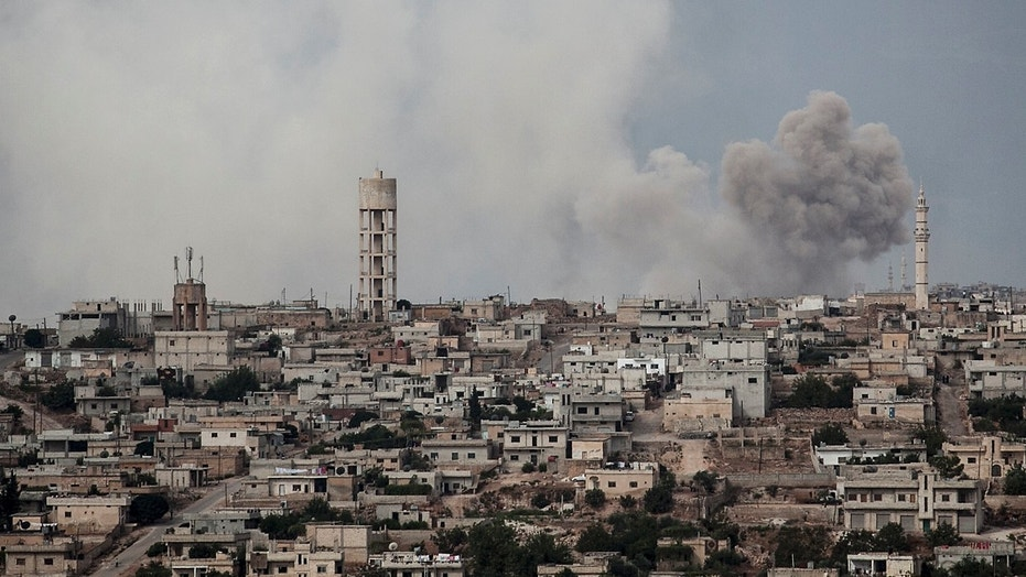 FILE 2013: smoke rises after a TNT bomb was thrown from a helicopter, hitting a rebel position during heavy fighting between troops loyal to president Bashar Assad and opposition fighters, in a neighbouring village to Kafr Nabuda, in the Idlib province.