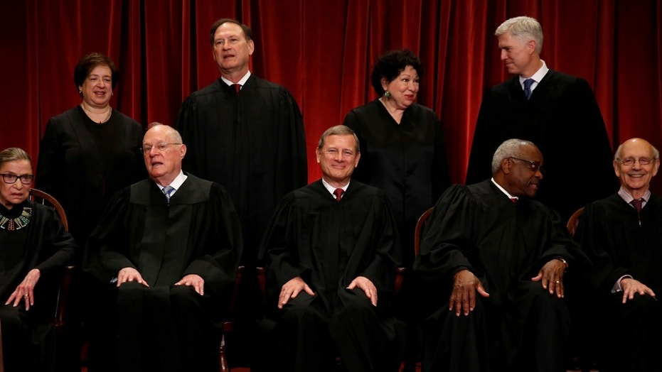U.S. Chief Justice John Roberts (seated C) leads Justice Ruth Bader Ginsburg (front row, L-R), Justice Anthony Kennedy, Justice Clarence Thomas, Justice Stephen Breyer, Justice Elena Kagan (back row, L-R), Justice Samuel Alito, Justice Sonia Sotomayor, and Justice Neil Gorsuch.