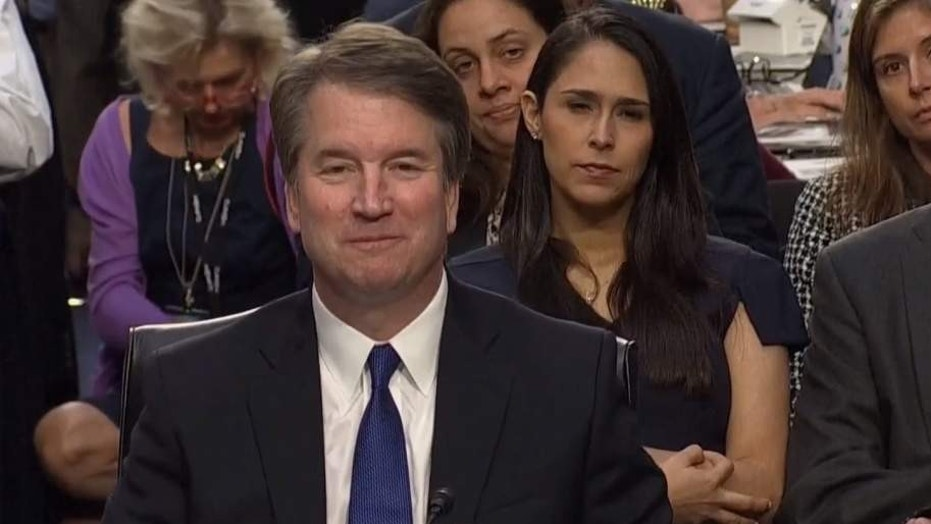 September 4, 2018: Zina Gelman Bash (right) was accused by liberal activists on Tuesday of being a white supremacist over an unintentional hand gesture she made during the confirmation hearing of Supreme Court nominee Brett Kavanaugh (left).