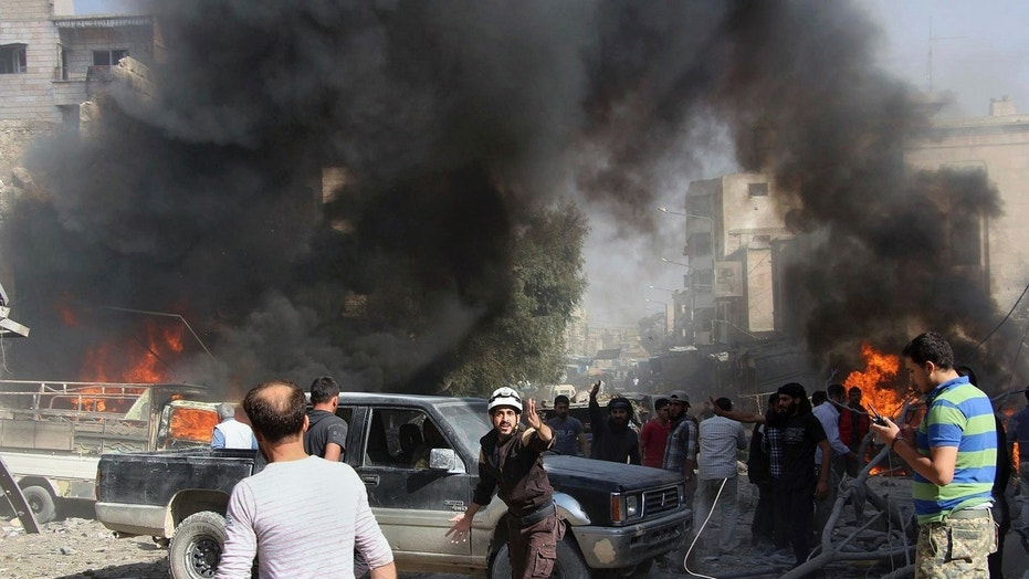 This file photo provided Sunday, Oct. 8, 2017 by the Syrian Civil Defense White Helmets, which has been authenticated based on its contents and other AP reporting, shows Civil Defense workers and Syrian citizens gathering after an airstrike hit a market in Maaret al-Numan in southern Idlib, Syria.