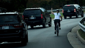 TOPSHOT - Juli Briskman gestures with her middle finger as a motorcade with US President Donald Trump departs Trump National Golf Course October 28, 2017 in Sterling, Virginia. / AFP PHOTO / Brendan Smialowski        (Photo credit should read BRENDAN SMIALOWSKI/AFP/Getty Images)