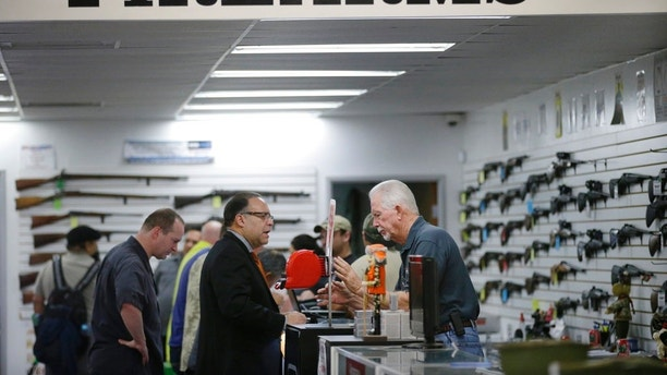 FILE - In this Dec. 9, 2015, file photo, sales associate Mike Conway, right, shows Paul Angulo a pistol at Bullseye Sport gun shop in Riverside, Calif. A U.S. judge has struck down a nearly century-old California law that banned gun shops from advertising handguns on their premises. Judge Troy Nunley in Sacramento ruled Tuesday, Sept. 11, 2018, that the law restricted speech in violation of the First Amendment. The ruling came in a lawsuit filed in 2014 by several gun dealers who were fined by the state for handgun ads. The 1923 law banned any handgun ads at gun shops that were visible from outside the store. Judge Nunley noted that gun shops could put up a 15-foot display of a sporting rifle or place ads for handguns elsewhere such as on a billboard blocks away. (AP Photo/Jae C. Hong, File)