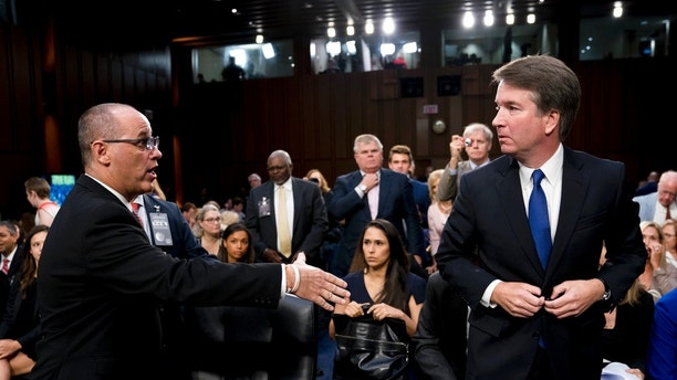 FILE - In this Tuesday, Sept. 4, 2018 file photo, Fred Guttenberg, the father of Jamie Guttenberg who was killed in the Stoneman Douglas High School shooting in Parkland, Fla., left, attempts to shake hands with President Donald Trump's Supreme Court nominee, Brett Kavanaugh, right, as he leaves for a lunch break while appearing before the Senate Judiciary Committee on Capitol Hill in Washington to begin his confirmation hearing. Kavanaugh did not shake his hand. Kavanaugh wrote in a response to questions from senators late Wednesday, Sept. 12, 2018, that he assumed the man had been a protester. (AP Photo/Andrew Harnik, File)