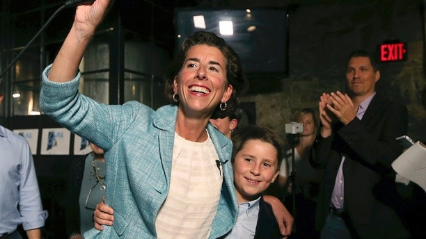 Incumbent Democratic Rhode Island Gov. Gina Raimondo waves to supporters alongside her son, Thompson, at her primary night victory party, Wednesday, Sept. 12, 2018, in Providence, R.I. (AP Photo/Elise Amendola)