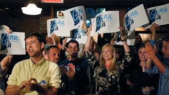 Supporters of incumbent Democratic Rhode Island Gov. Gina Raimondo cheer as they watch results on TV at her primary night party, Wednesday, Sept. 12, 2018, in Providence, R.I. (AP Photo/Elise Amendola)