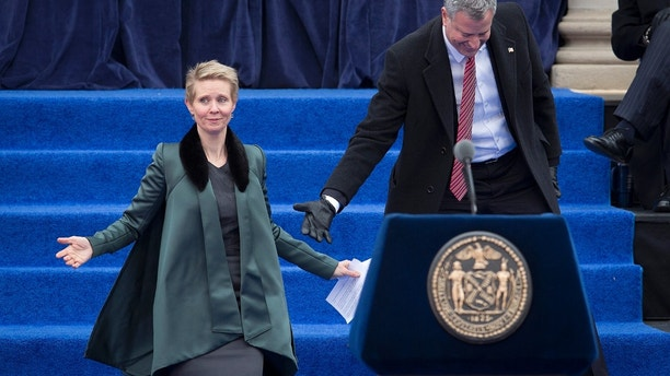 """Actress Cynthia Nixon is helped down the stairs by new mayor Bill de Blasio's during his inauguration ceremony for the mayor of New York at City Hall in New York January 1, 2014. Bill de Blasio was formally inaugurated as New York City's 109th mayor on Wednesday at a City Hall ceremony where he promised to take """"dead aim"""" at closing the affordability gap he has decried as New York's tale of two cities.   REUTERS/Carlo Allegri (UNITED STATES - Tags: POLITICS SOCIETY ENTERTAINMENT) - GM1EA120GCP01"""