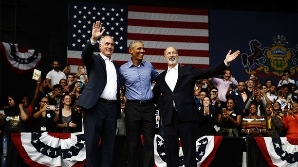 Former President Barack Obama, center, stands with Sen. Bob Casey D-Pa., left, and Gov. Tom Wolf, during a campaign rally in Philadelphia, Friday, Sept. 21, 2018. (AP Photo/Matt Rourke)