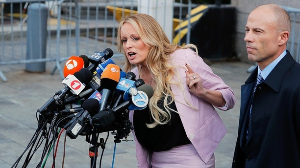 Adult film actress Stephanie Clifford, also known as Stormy Daniels, speaks to media along with lawyer Michael Avenatti (R) outside federal court in the Manhattan borough of New York City, New York, U.S., April 16, 2018. REUTERS/Lucas Jackson - HP1EE4G1NGLO1