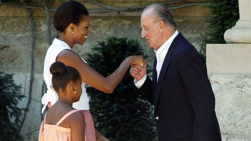 U.S. first lady Michelle Obama is greeted by Spain's King Juan Carlos as her daughter Sasha looks on before their lunch at Marivent Palace in Palma de Mallorca August 8, 2010. REUTERS/Enrique Calvo (SPAIN - Tags: ROYALS POLITICS IMAGES OF THE DAY)