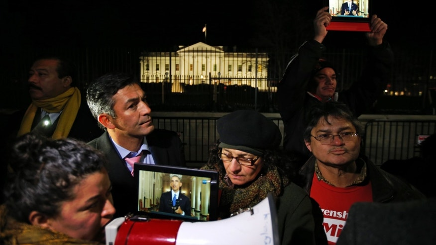 Rosa Lozano, from Washington, left, translates the speech into Spanish as others listen to President Obama's speech on tablets, during a demonstration in front of the White House in Washington, Thursday, Nov. 20, 2014. President Barack Obama announced executive actions on immigration during a nationally televised address. (AP Photo/Alex Brandon)