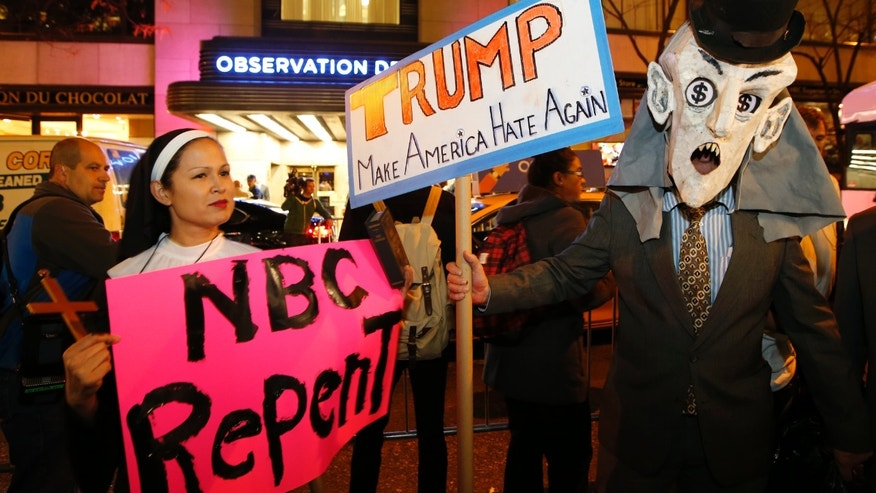 "Protesters opposed to the appearance of Republican presidential candidate Donald Trump as a guest host on this weekend's ""Saturday Night Live,"" demonstrate in front of NBC Studios where the television show is taped and broadcast, Wednesday, Nov. 4, 2015, in New York.  (AP Photo/Kathy Willens)"
