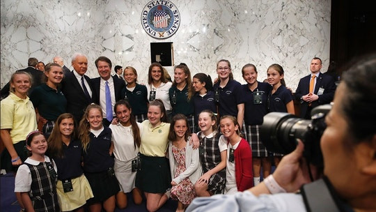 Brett Kavanaugh, President Donald Trump's Supreme Court nominee, fourth from top left, stands with Sen. Orrin Hatch, R-Utah, and girls who he has coached in basketball, including his daughters Liza, bottom left, and Margaret, second from top right, as they pose for a photograph during a break in the third day of his Senate Judiciary Committee confirmation hearing, Thursday, Sept. 6, 2018, on Capitol Hill in Washington, to replace retired Justice Anthony Kennedy. (AP Photo/Jacquelyn Martin)