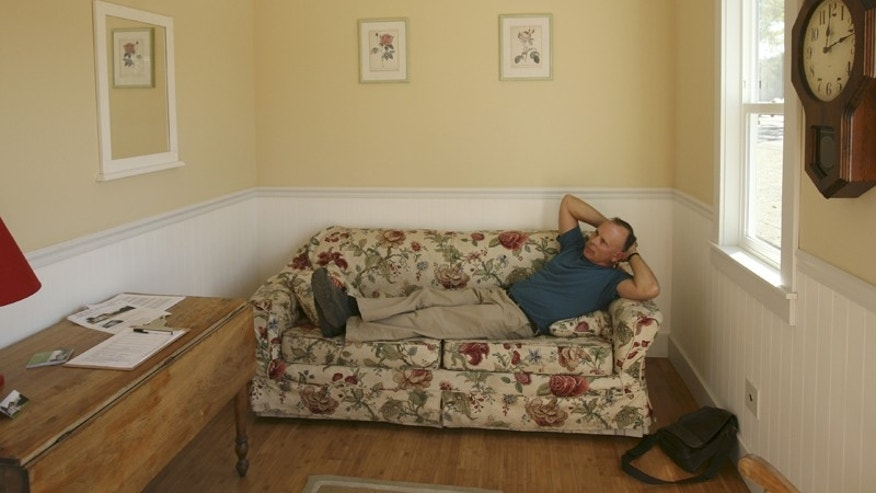 Stephen Marshall, owner of Little House on the Trailer, relaxes in one of his one room houses in Petaluma, Calif.