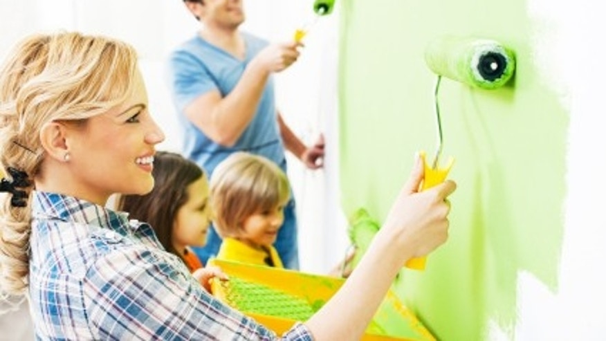 Portrait of a happy family holding paint rollers and painting wall in green.