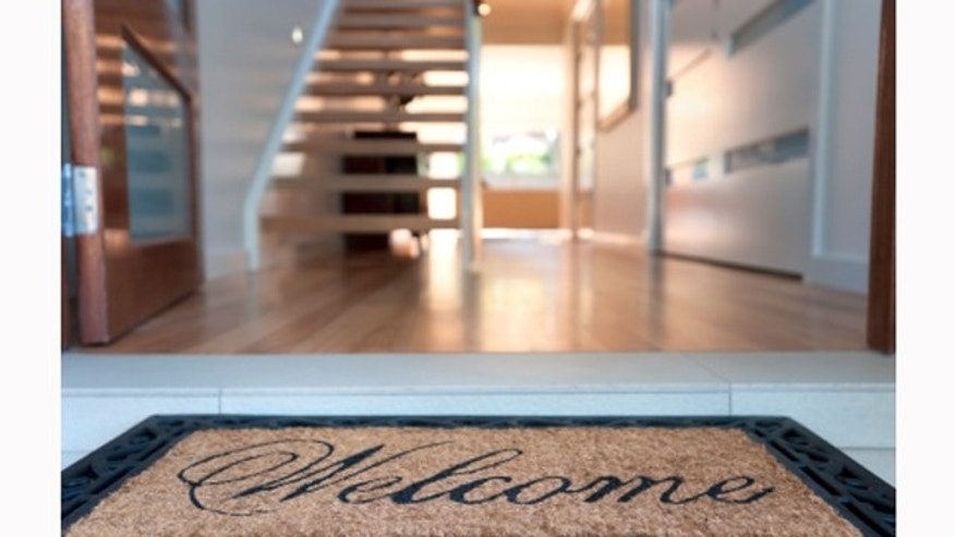 Close up of a welcome mat in front of an inviting house.
