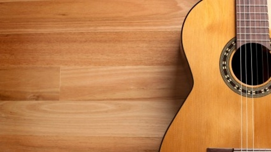 Acoustic guitar with wood background and copy space.