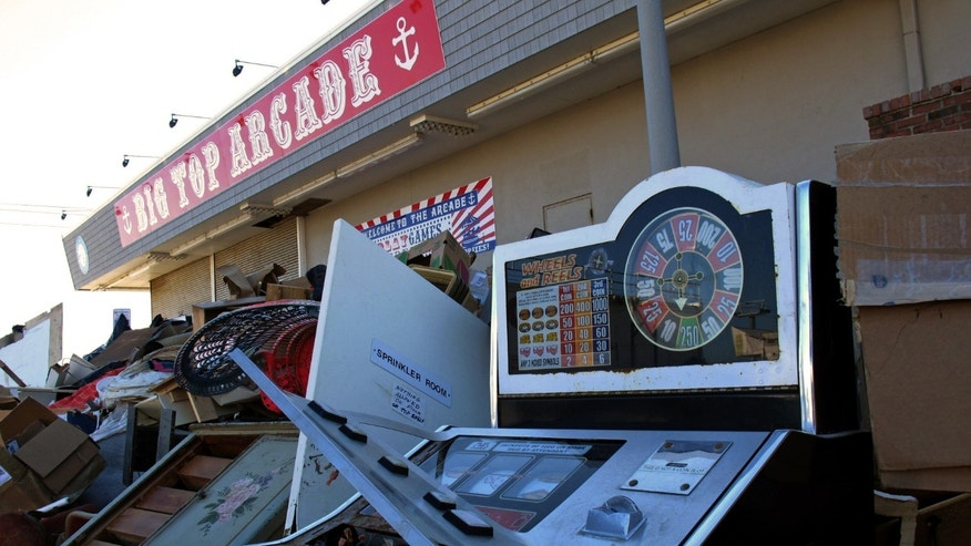 Flood-damaged arcade games sit in a pile of debris near the beach in Seaside Heights, N.J. on Monday, Jan. 7, 2013, the first day that some of the hardest-hit sections of the Jersey shore allowed residents to move back home permanently after Superstorm Sandy. (AP Photo/Wayne Parry)