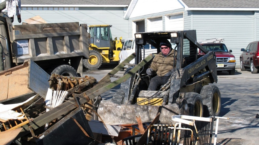 A worker uses a small front-end loader to remove Superstorm Sandy debris from the front of a home in Seaside Heights, N.J. on Monday, Jan. 7, 2013. Monday was the first day that some of the hardest-hit parts of the Jersey shore allowed residents to begin moving back home for good. (AP Photo/Wayne Parry)