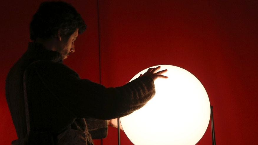 "A man touches a lamp called ""Light Sister"" on display at the Milan Design Fair, in Milan, Italy, Thursday, April 11, 2013. The Milan furniture and design week fair, showcasing the latest in furniture and design from countries around the world, will continue until Sunday. (AP Photo/Antonio Calanni)"