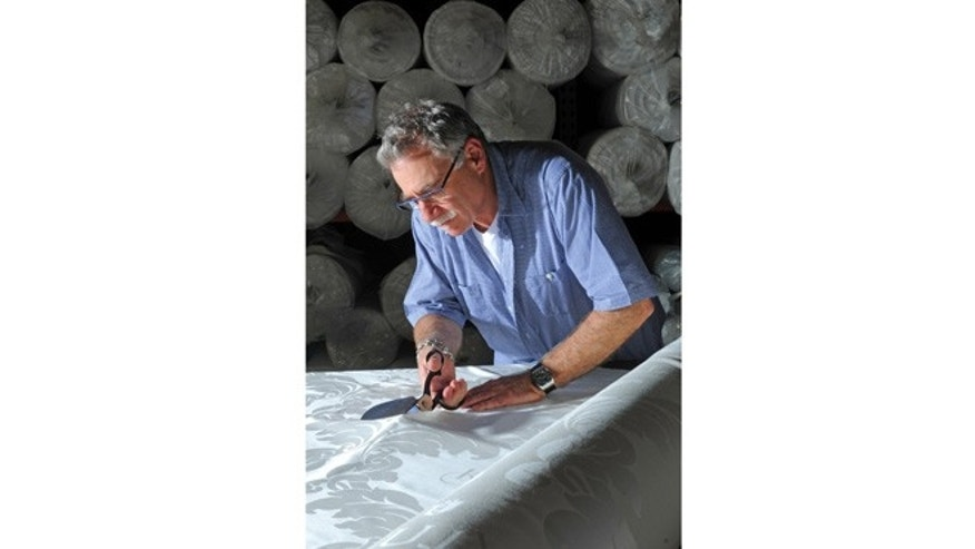 Undated image of Earl S. Kluft cutting fabric for one of the models in his luxury mattress brand.