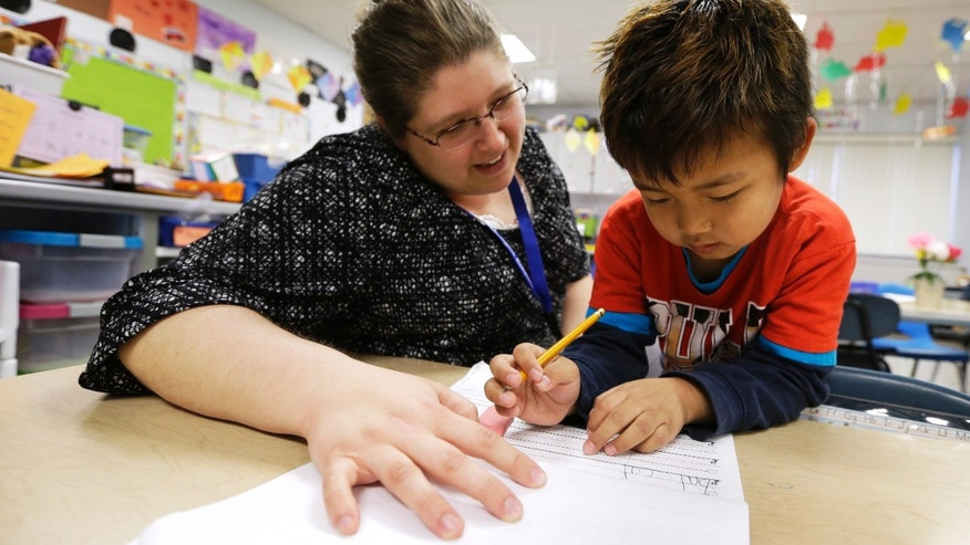 Roundy Elementary School kindergarten teacher Jennifer Young works with student Nang Zam Lian, in Columbus Junction, Iowa on Wednesday, April 17, 2013. Tyson Food's decision to recruit refugees from Myanmar marks a new chapter in this southeast Iowa meatpacking town. (AP Photo/Charlie Neibergall)