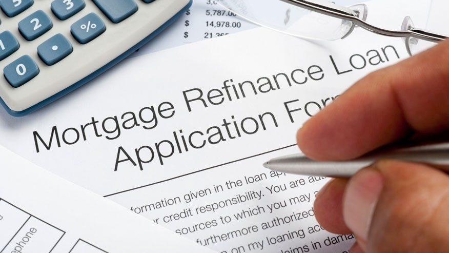 Mortgage Refinance Application Form with pen, calculator, writing hand