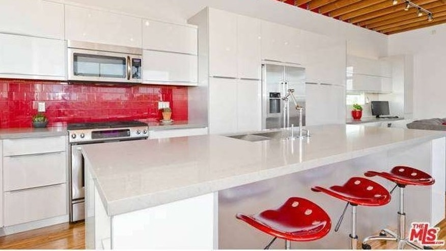 Like the rest of the home, the kitchen features splashes of red on white.