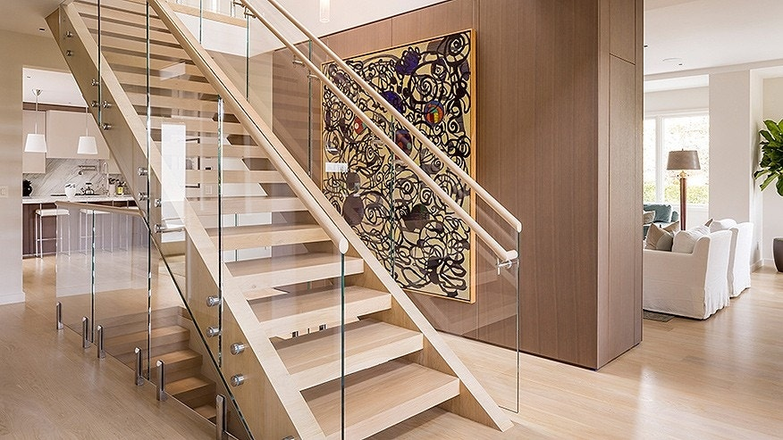 A glass-and-wood staircase connects the four floors.