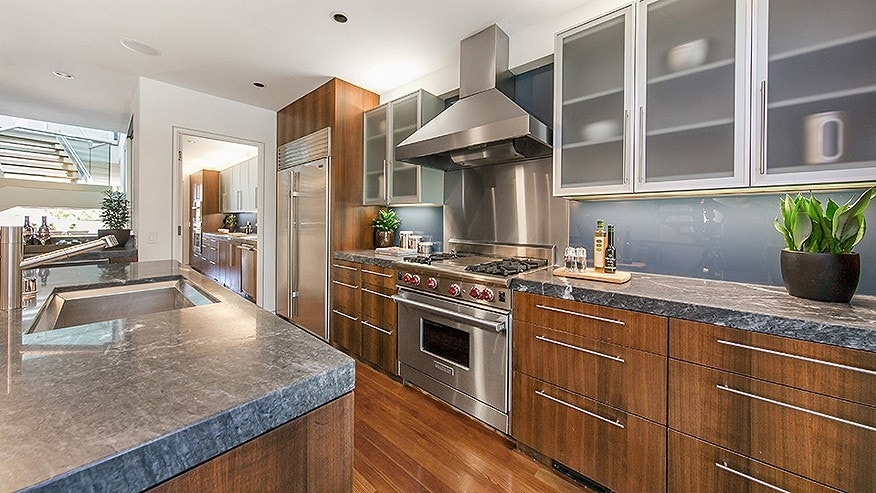 The kitchen features marble countertops, custom cabinetry and high-end appliances.