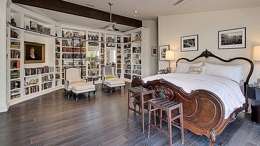 The master suite includes a library, as well as access to a patio with a fountain.