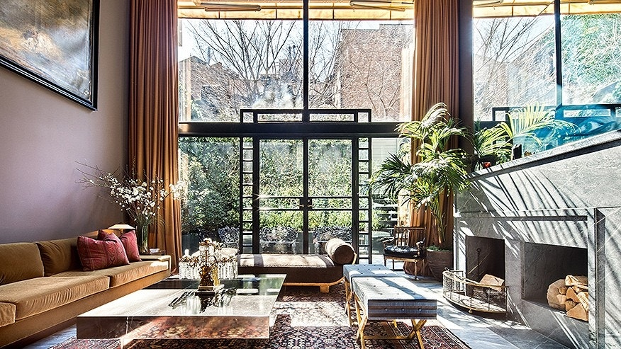 The two-story living room faces the garden and has a wood-burning fireplace. 'There are curtains that draw open like a production is about to begin,' said listing agent Jeremy Stein.