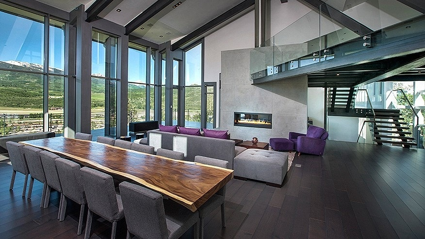 A fireplace separates the sitting area from the living and dining areas. A loft with glass railings stretches across the room.