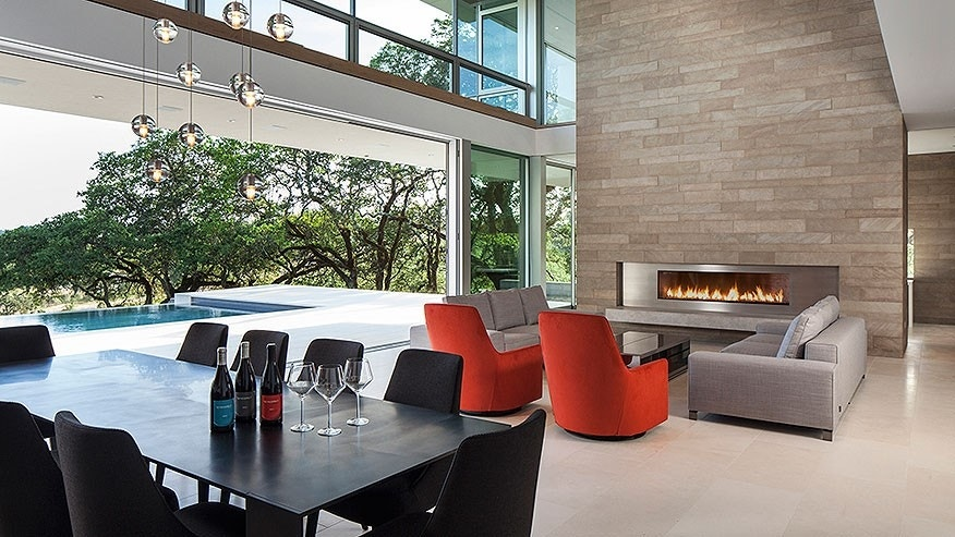An indoor balcony stretches above the living room. Floor-to-ceiling glass walls open to a limestone terrace.