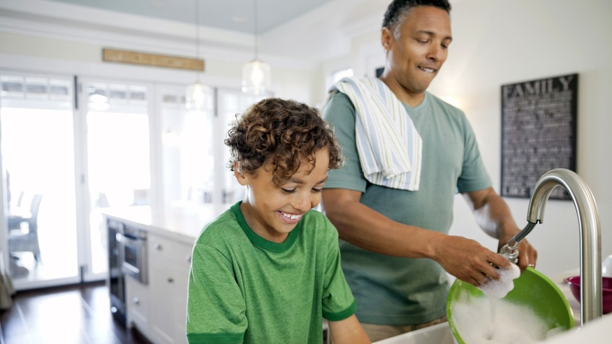 father and son washing dishes together at kitchen sink
